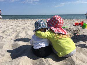 Geschwister: Grosse Schwester umarmt ihren kleinen Bruder am Strand