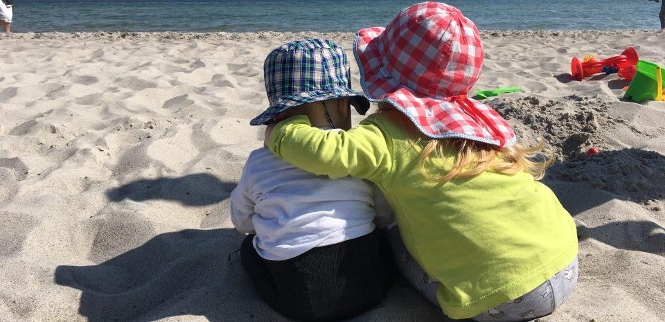 Grosse Schwester umarmt ihren kleinen Bruder am Strand